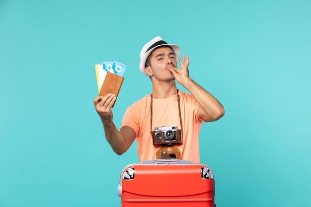 Vooraanzicht man in vakantie met zijn kaartjes op lichtblauw