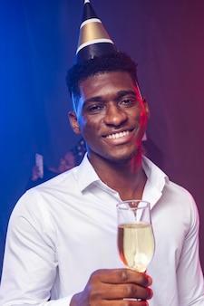 Vooraanzicht man met feestmuts en met een glas