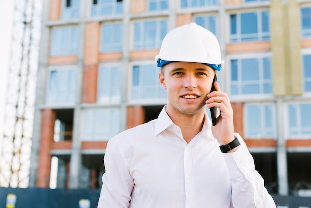 Vooraanzicht man met helm praten aan de telefoon