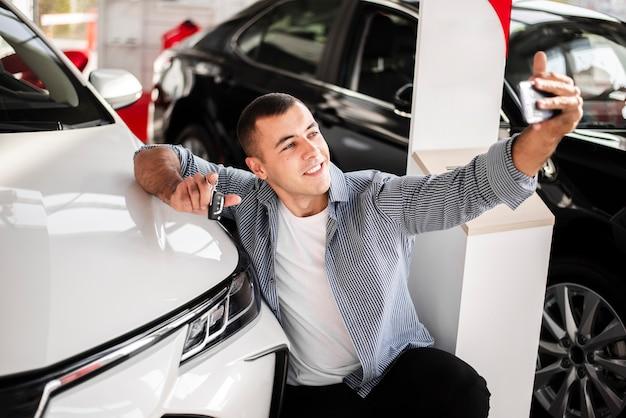 Vooraanzicht man nemen een selfie met een auto