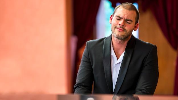 Vooraanzicht man piano spelen binnenshuis