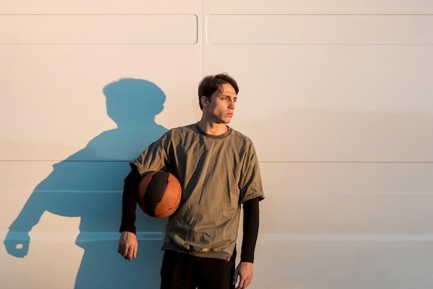 Vooraanzicht man poseren met een basketbal