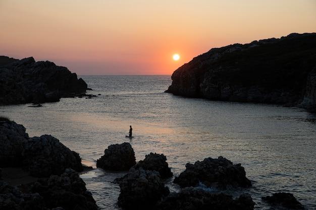 Vooraanzicht man surfen bij zonsondergang