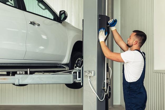 Vooraanzicht man tillen auto voor inspectie