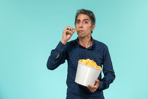 Vooraanzicht man van middelbare leeftijd met mand vol cips en eten op het blauwe oppervlak