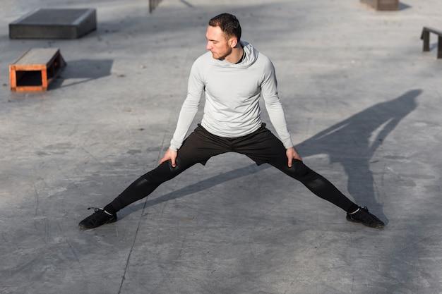 Vooraanzicht man warming-up zijn benen