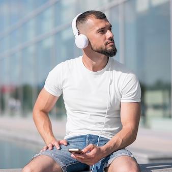 Vooraanzicht man wegkijken tijdens het luisteren naar muziek