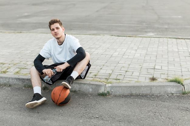 Vooraanzicht man zit met een basketbal