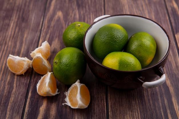 Vooraanzicht mandarijnen in een pan op een houten muur