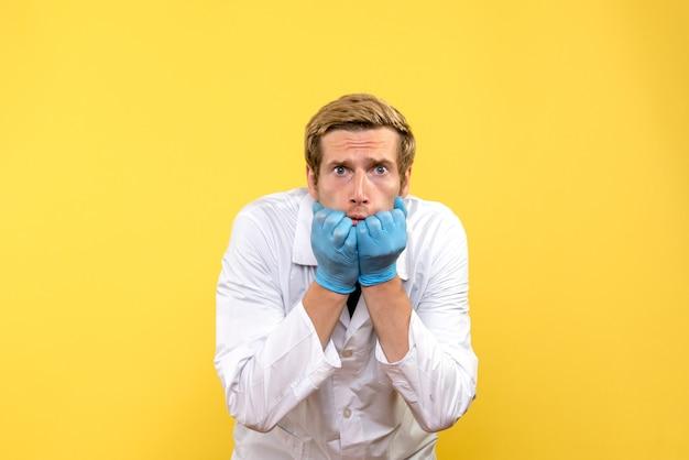 Vooraanzicht mannelijke arts bang op gele achtergrond medic pandemie covid mens