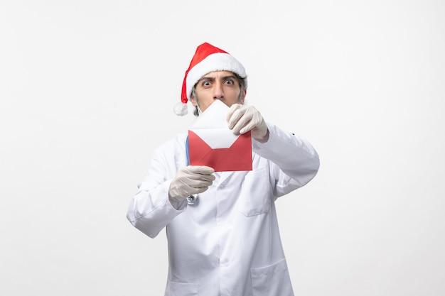Vooraanzicht mannelijke arts bedrijf omhult op witte muur virus emotie covid-gezondheid