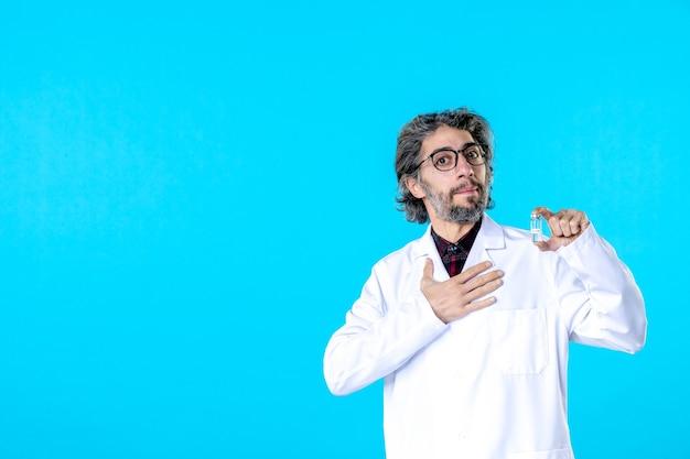 Vooraanzicht mannelijke arts die een flesje op blauw houdt