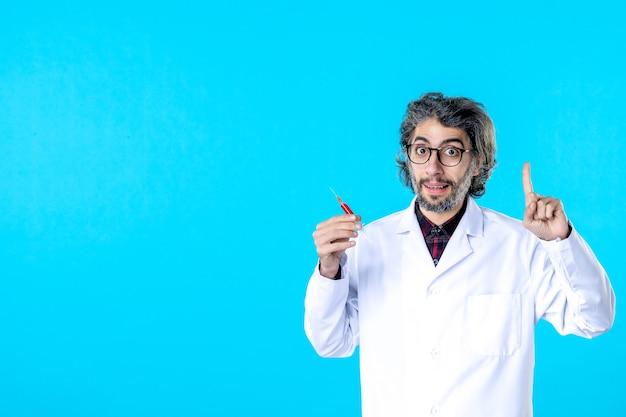 Vooraanzicht mannelijke arts die injectie houdt op blauw medisch ziekenhuis covid virus wetenschap gezondheid