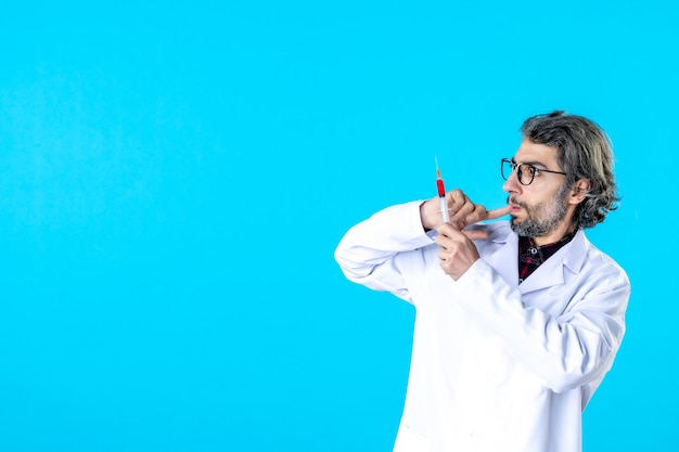 Vooraanzicht mannelijke arts die injectie op blauw houdt