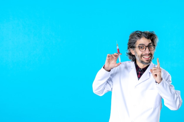 Vooraanzicht mannelijke arts die injectie op blauw voorbereidt