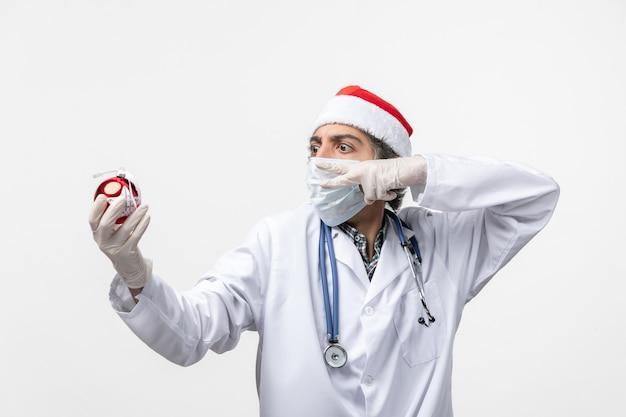 Vooraanzicht mannelijke arts die nieuwjaar boom speelgoed gezondheid covid virus houdt