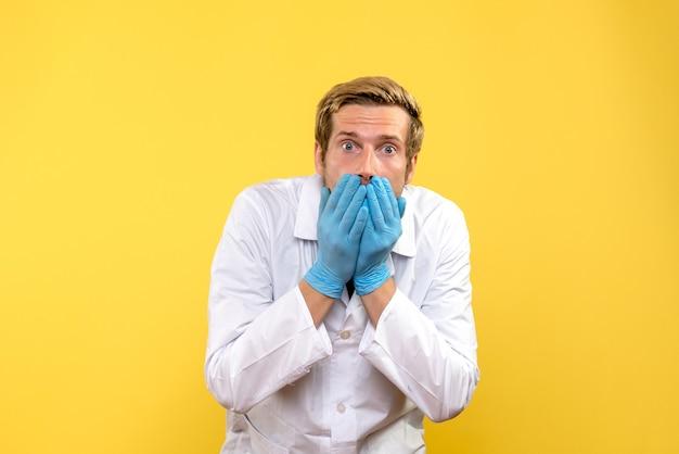 Vooraanzicht mannelijke arts geschokt op gele achtergrond menselijke covid-ziekenhuis medic