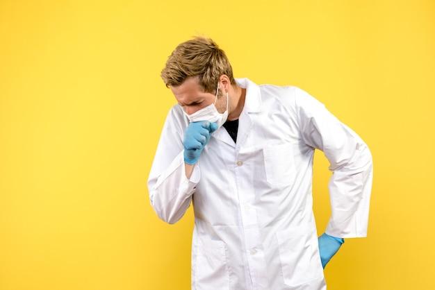Vooraanzicht mannelijke arts hoesten op gele achtergrond pandemische covid gezondheid medic