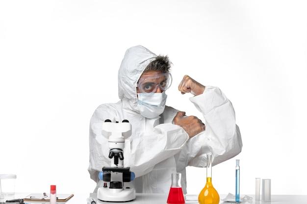 Vooraanzicht mannelijke arts in beschermend pak en masker buigen op witte achtergrond pandemisch covid gezondheidsvirus
