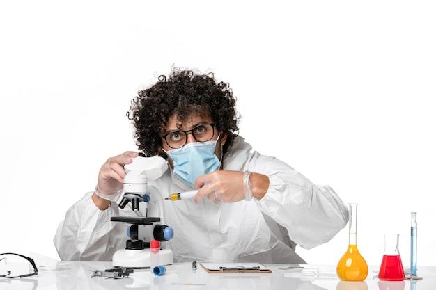 Vooraanzicht mannelijke arts in beschermend pak en masker met injectie op wit