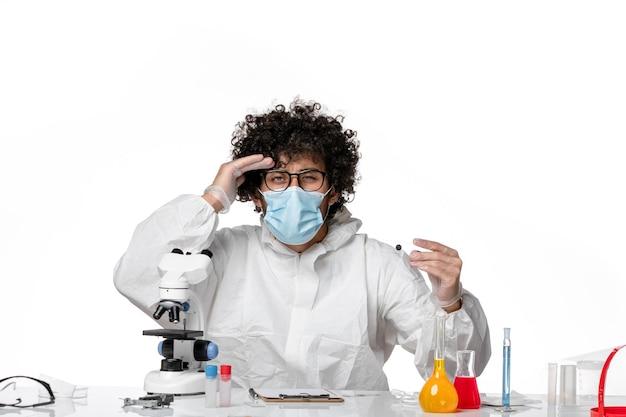 Vooraanzicht mannelijke arts in beschermend pak en masker met monster op lichtwit
