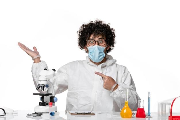 Vooraanzicht mannelijke arts in beschermend pak en masker zit gewoon met oplossingen op wit