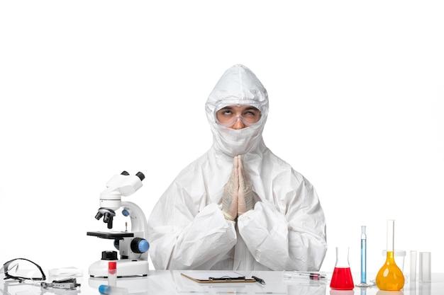 Vooraanzicht mannelijke arts in beschermend pak en met masker bidden op witte ruimte