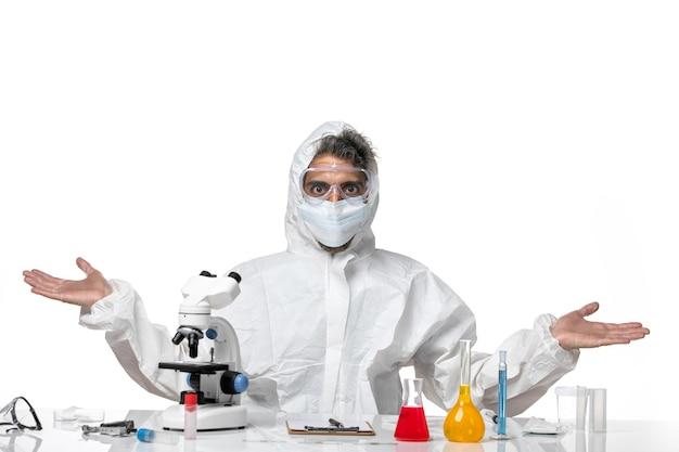 Vooraanzicht mannelijke arts in beschermend pak en met steriel masker poseren op wit