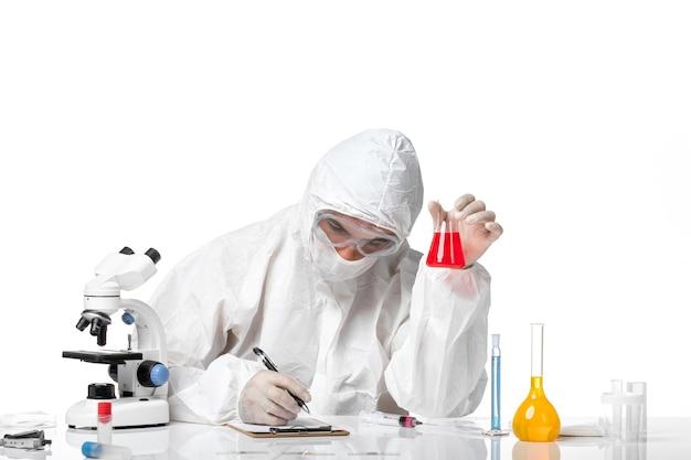 Vooraanzicht mannelijke arts in beschermend pak met masker vanwege covid bedrijf kolf met rode oplossing op witte ruimte