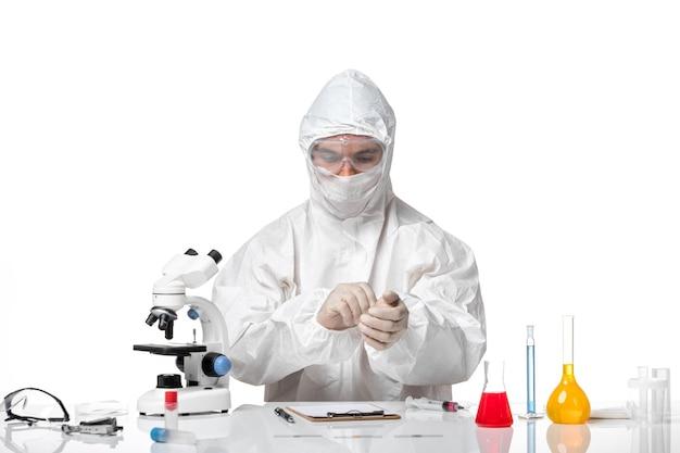 Vooraanzicht mannelijke arts in beschermend pak met masker vanwege covid handschoenen dragen op witte ruimte