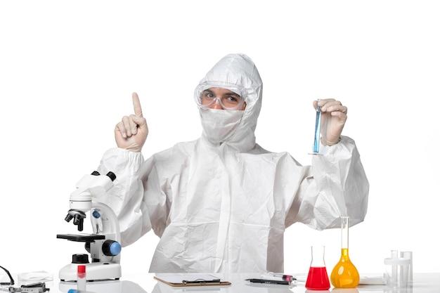 Vooraanzicht mannelijke arts in beschermend pak met masker vanwege covid holding kolf met blauwe oplossing op wit bureau