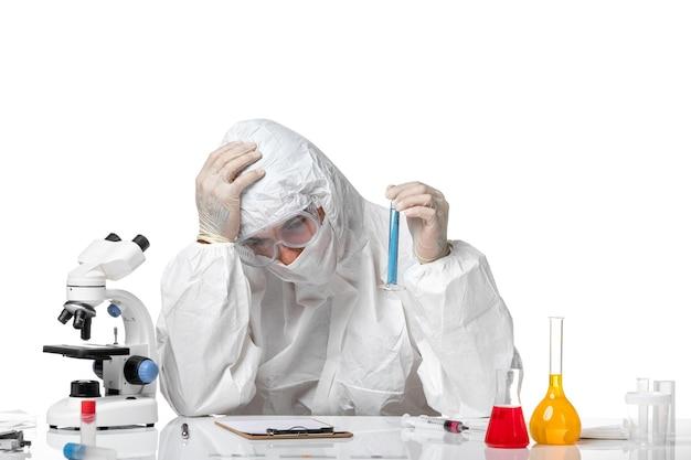 Vooraanzicht mannelijke arts in beschermend pak met masker vanwege covid-kolf met blauwe oplossing moe op een lichtwitte ruimte