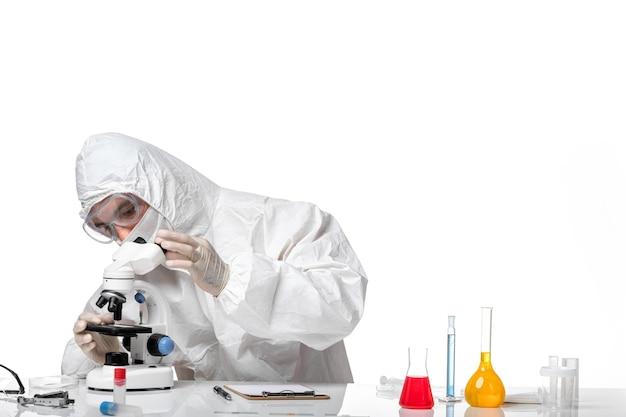 Vooraanzicht mannelijke arts in beschermend pak met masker vanwege covid met behulp van microscoop op witte ruimte