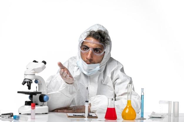 Vooraanzicht mannelijke arts in beschermend pak poseren op wit