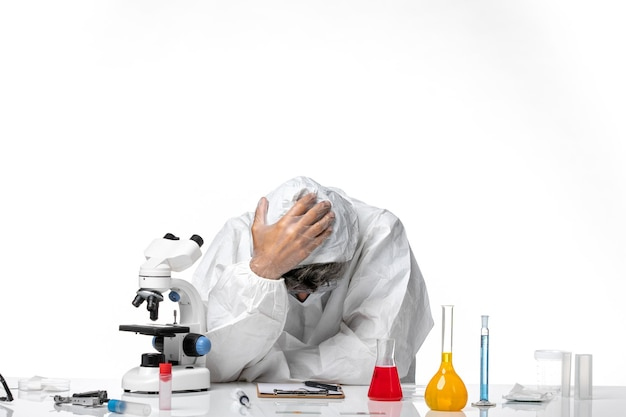 Vooraanzicht mannelijke arts in beschermend pak voelt zich moe op wit