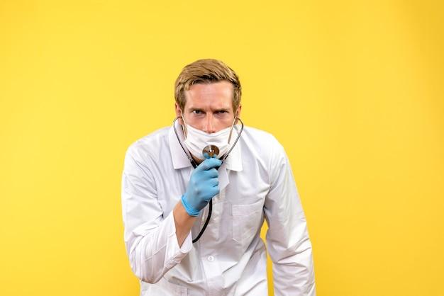 Vooraanzicht mannelijke arts in masker met stethoscoop op gele achtergrond pandemische covid gezondheid