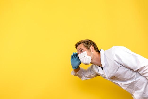 Vooraanzicht mannelijke arts in masker op gele achtergrond covid pandemische gezondheid