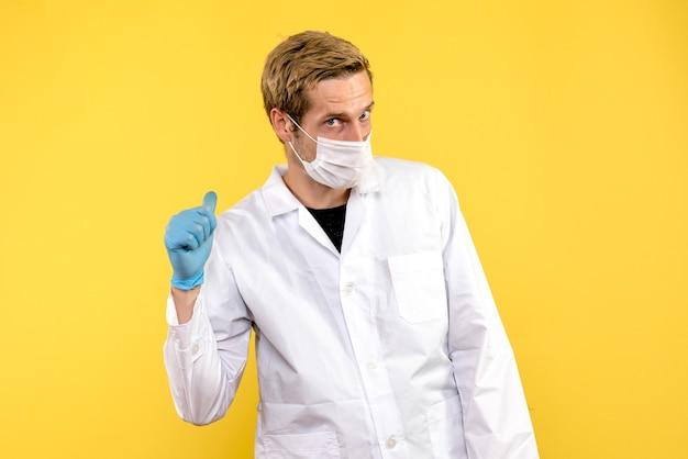 Vooraanzicht mannelijke arts in masker op gele achtergrond covid pandemische gezondheidsdokter
