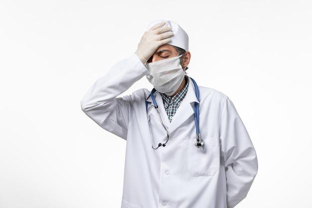 Vooraanzicht mannelijke arts in medisch pak en masker vanwege coronavirus met hoofdpijn op wit oppervlak