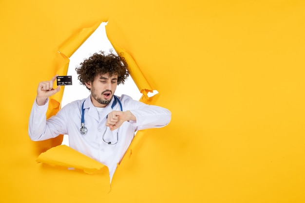 Vooraanzicht mannelijke arts in medisch pak met bankkaart op gele gescheurde kleur medic gezondheid geneeskunde virus ziekenhuis