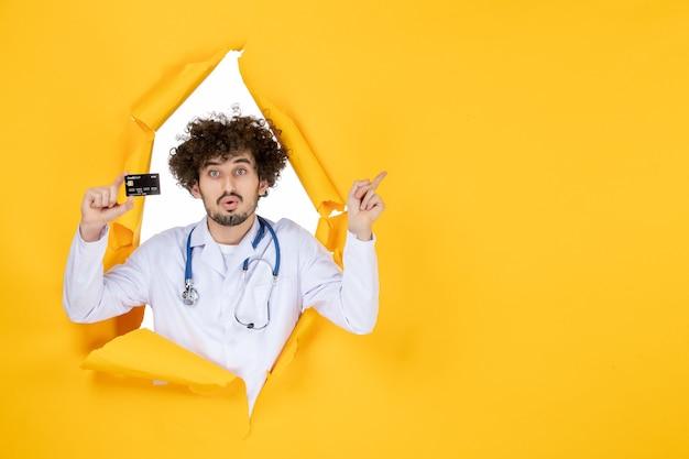 Vooraanzicht mannelijke arts in medisch pak met bankkaart op gele gescheurde kleur medic gezondheid geneeskunde ziekenhuisziekte