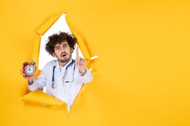 Vooraanzicht mannelijke arts in medisch pak met klokken op geel ziekenhuis winkelen geneeskunde kleur tijd gezondheid