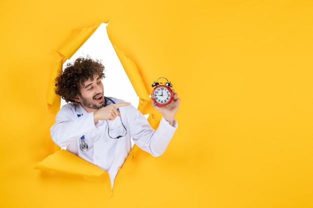 Vooraanzicht mannelijke arts in medisch pak met klokken op gele gezondheidskleur winkelen geneeskunde tijd medic