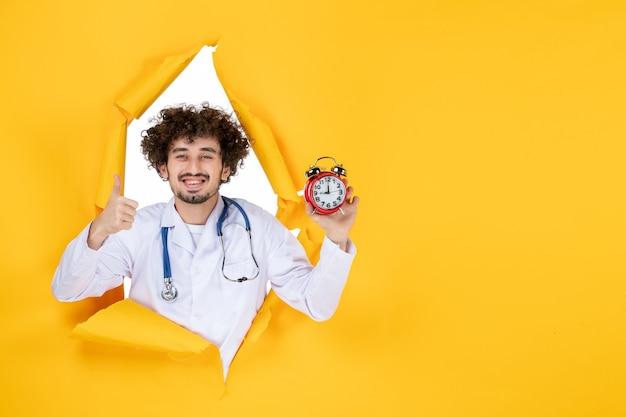 Vooraanzicht mannelijke arts in medisch pak met klokken op gele gezondheidskleur ziekenhuis geneeskunde tijd medic