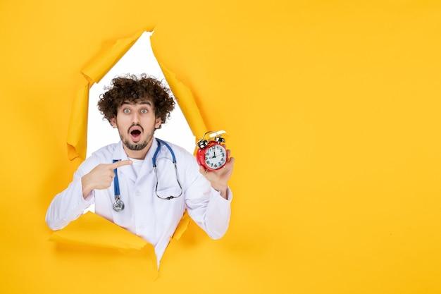Vooraanzicht mannelijke arts in medisch pak met klokken op gele gezondheidskleur ziekenhuis medic geneeskunde tijd