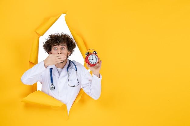 Vooraanzicht mannelijke arts in medisch pak met klokken op gele gezondheidsziekenhuisarts die medicijnen winkelt