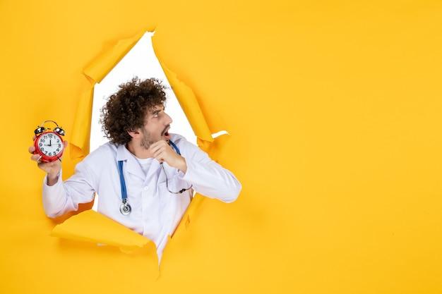 Vooraanzicht mannelijke arts in medisch pak met klokken op gele kleuren ziekenhuisgeneeskunde tijd medic gezondheid