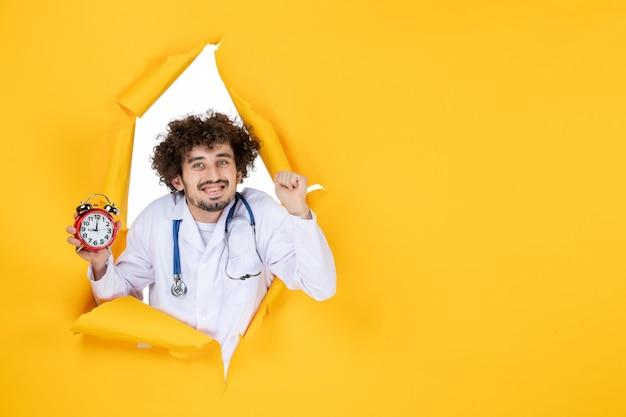 Vooraanzicht mannelijke arts in medisch pak met klokken op gele medicijnkleur gezondheidstijd ziekenhuisvirus