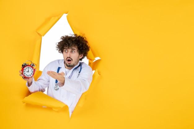 Vooraanzicht mannelijke arts in medisch pak met klokken op gele medicijnkleur medic gezondheidstijd ziekenhuisvirus