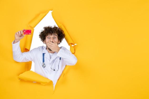 Vooraanzicht mannelijke arts in medisch pak met rode bankkaart op gele geneeskunde ziekenhuisziekte virus medic geld gezondheid